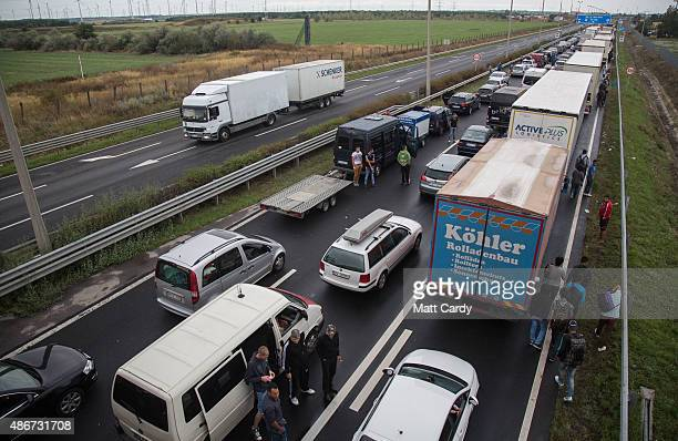 Migrants pass as vehicles queue to cross the border from Hungary into Austria on September 5 2015 near Nickelsdorf Austria Last night the Hungarian...