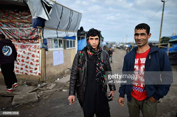 Migrants pose for a photograph as they contend with wintery conditions in the camp known as the 'New Jungle' on December 2 2015 in Calais France...