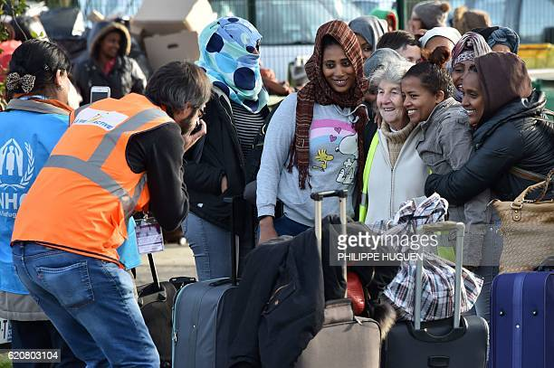 Migrants pose for a photograph with a volunteer as they leave the 'Jules Ferry' reception centre next to the recently demolished 'Jungle' migrant...