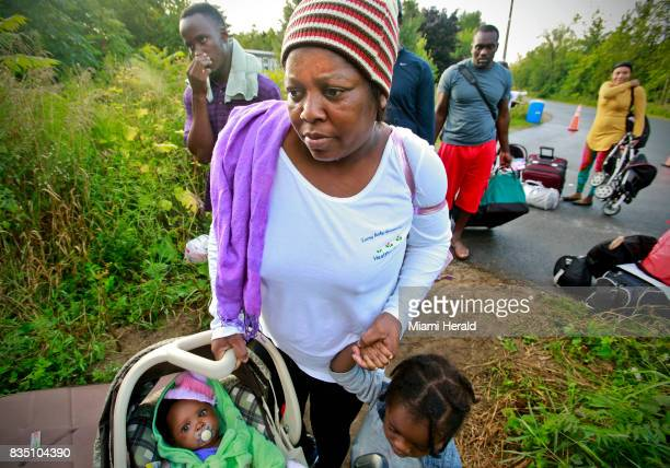 Migrants prepare to cross from US to Canada at the border along Roxham Road on Sunday Aug 13 2017 Thousands of people have crossed over into Canada...