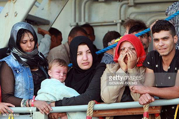 Migrants prepare to disembark from the Irish Military ship LE Niamh upon its arrival in the port of Messina on July 29 2015 More than 1800 migrants...