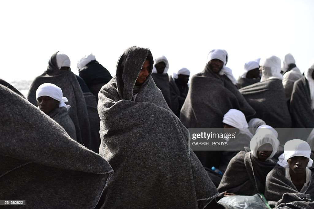 Migrants protect themselves from the cold with blankets as they wait to arrive in the port of Cagliari, Sardinia, on May 26, 2016 aboard the rescue ship 'Aquarius', two day after their rescue off the Libyan coasts. The Aquarius is a former North Atlantic fisheries protection ship now used by humanitarians SOS Mediterranee and Medecins Sans Frontieres (Doctors without Borders) which patrols to rescue migrants and refugees trying to reach Europe crossing the Mediterranean sea aboard rubber boats or old fishing boat. / AFP / GABRIEL