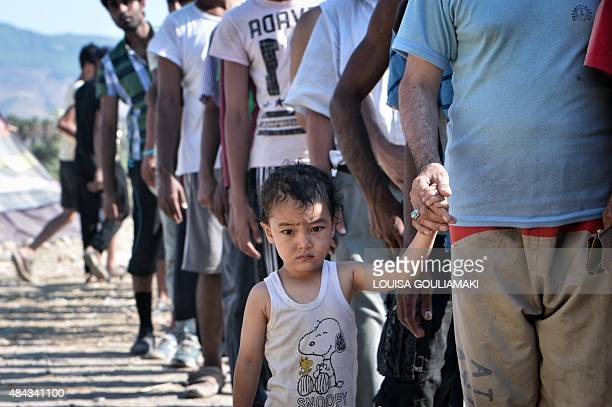 Migrants queue during a food distribution organized by the local organisation 'Kos solidarity' outside the abandoned Captain Elias hotel where...