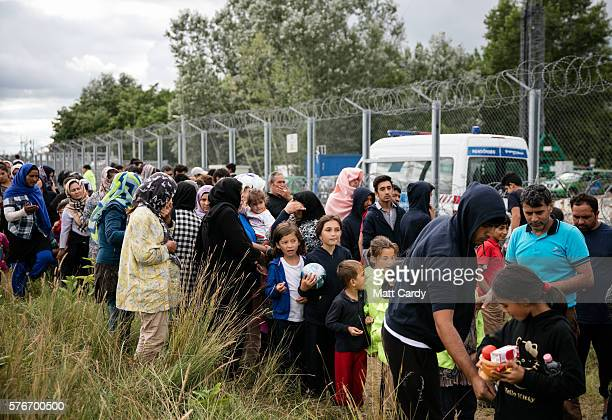 Migrants queue for food being delivered by volunteers at a camp besides the border fence close to the E75 Horgas border crossing between Serbia and...