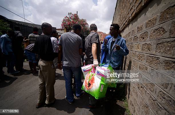 Migrants queue for food outside 'Baobab' migration centre next to the Tiburtina train station in Rome on June 14 2015 Hundreds of migrants mainly...