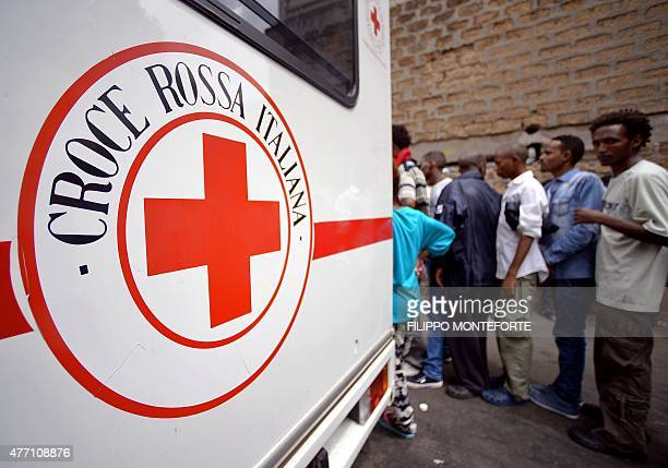 Migrants queue near a vehicle of the Italian Red Cross outside 'Baobab' migration centre next to the Tiburtina train station in Rome on June 14 2015...