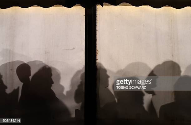 TOPSHOT Migrants queue up at a waiting tent to register at the State Office of Health and Social Affairs centre in Berlin on early January 5 2016 /...