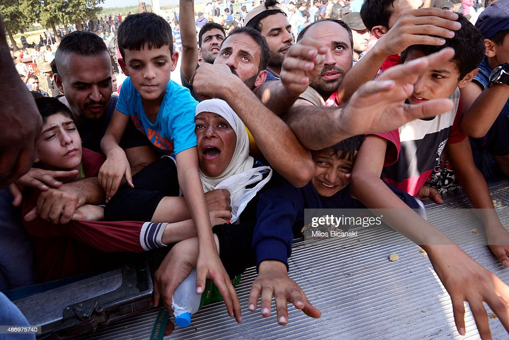 Migrants reach for food delivered by the Caritas humanitarian organisation on September 5 2015 in Idomeni Greece Several thousand migrants without...