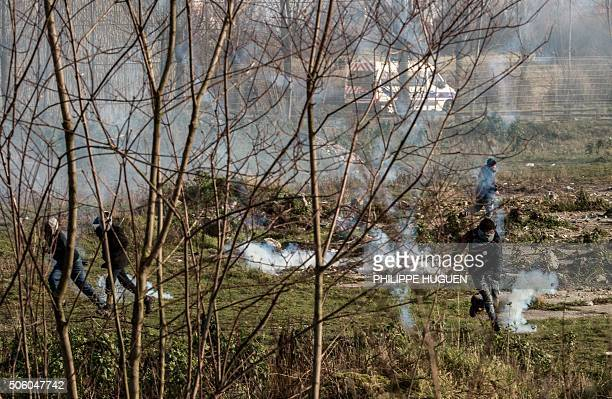 Migrants react as French riot police guarding trucks throw tear gas after migrants tried to board trucks near the A16 motorway near the site of the...