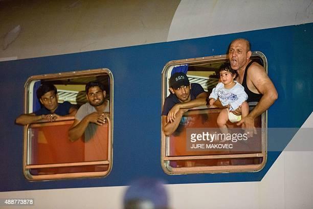 Migrants react as they wait in a train at the railway station near the SlovenianCroatian border in Dobova Brezice on September 17 2015 Slovenia...