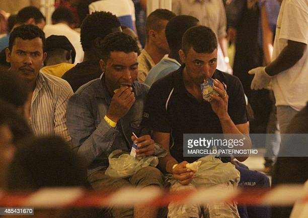 Migrants receive food after they disembarked from Swedish Coast Guards ship 'Poseidon' in the port of Palermo on August 27 2015 following a rescue...