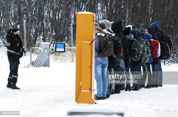Migrants receive instructions from a Norwegian police officer at Storskog boarder crossing station near Kirkenes after crossing the boarder between...