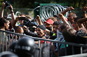Migrants remonstrate with Hungarian riot police as an attempt is made to break the border post gate and pull down the razor wire fence on September...