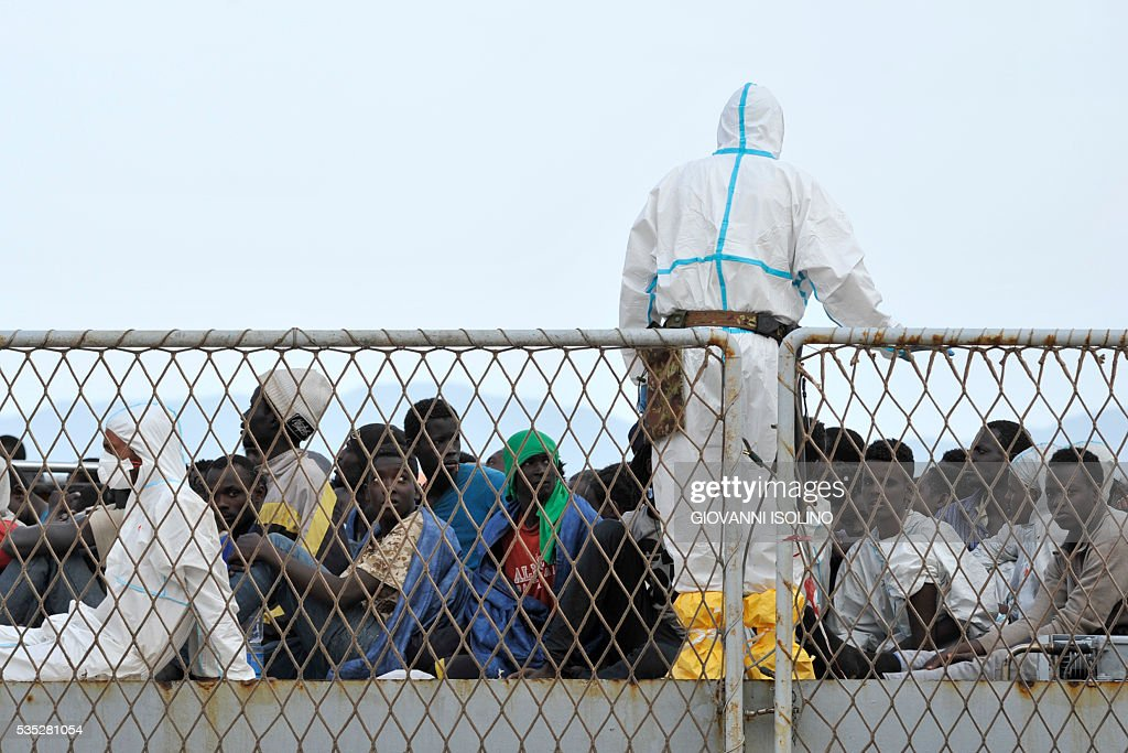 Migrants rescued at sea arrive aboard the Italian Navy ship 'Vega' on May 29, 2016 in the port of Reggio Calabria, southern Italy. A week of shipwrecks and death in the Mediterranean culminated today with harrowing testimony from migrant survivors who said another 500 people including 40 children had drowned, bringing the number of feared dead to 700. / AFP / GIOVANNI