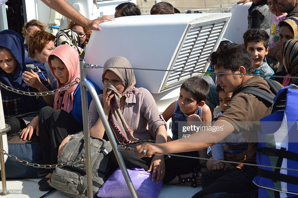 Migrants rescued by coastguards sit on a rescue boat before disembarking near the town of Ierapetra on the Greek island of Crete on July 9, 2013. The Greek coastguard rescued 131 off the island of Crete after their boat began to take on water, port authorities said.