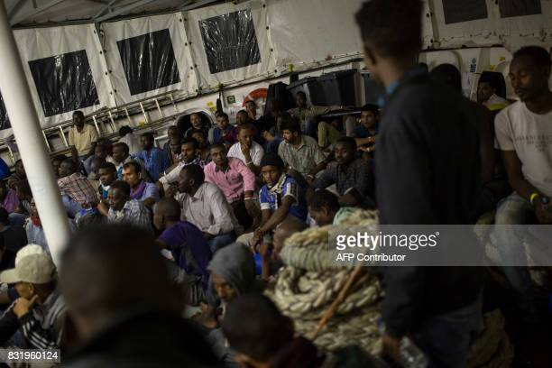Migrants rest on the deck of the Aquarius rescue ship run by NGO SOS Mediterranee and Medecins Sans Frontieres after their transfer from the NGO...