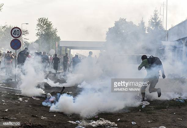 Migrants run away from tear gas thrown by Hungarian antiriot police officers at the Hungarian border with Serbia near the town of Horgos on September...