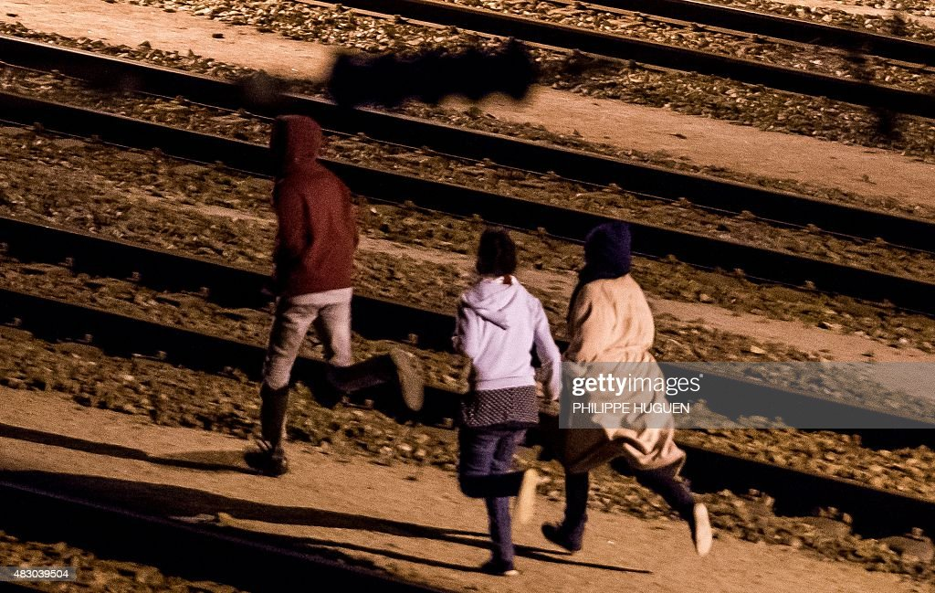 Migrants run on rail tracks in the Channel Tunnel site in Frethun, northern France, on August 5, 2015. The European Commission offered August 4 to help France and Britain deal with the migrant crisis at the Channel Tunnel, as police on both sides braced for new attempts at the crossing.