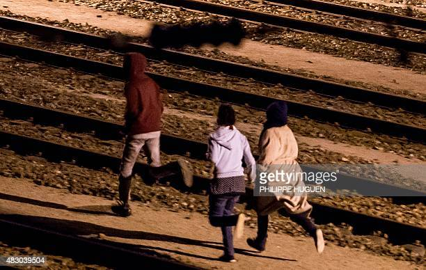 Migrants run on rail tracks in the Channel Tunnel site in Frethun northern France on August 5 2015 The European Commission offered August 4 to help...