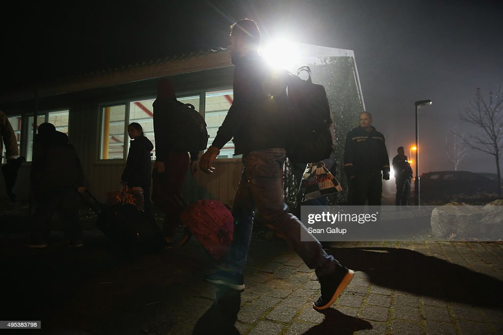 Migrants seeking asylum in Germany arrive by bus a a former office park that has become short-term accommodation for migrants on November 2, 2015 in Sumte, Germany. Sumte, a farming village located southwest of Hamburg, has a population of 102, and starting later today it is to receive 500 migrants who will be housed in an abandoned office park on the village edge. The number of migrants at the shelter could reach up to 750 in coming weeks as Germany struggles to accommodate the unrelenting flood of migrants arriving at a rate of thousands per day. Authorities are distributing migrants seeking asylum in Germany at shelters nationwide, both in urban centers and in small, rural communities.