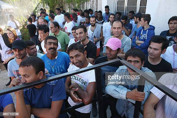 Migrants seeking asylum in Germany listen to a band perform during a summer fest for migrants and locals at the Bayernkaserne asylum shelter on...