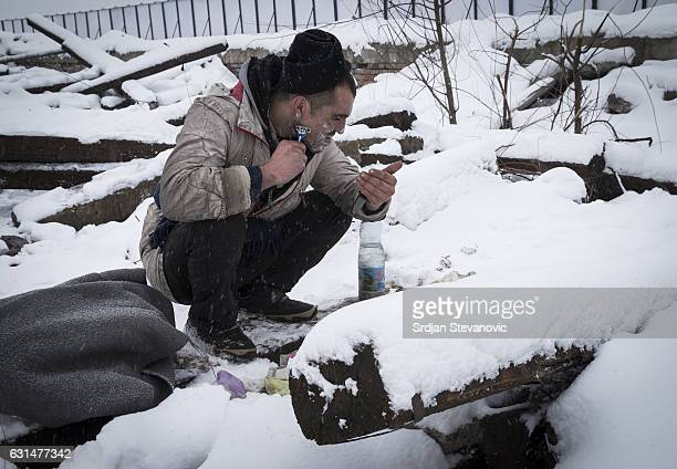 A migrants shaves surrounded by snow outside a derelict customs warehouse on January 11 2017 in Belgrade Serbia It is estimated that around 1 000...