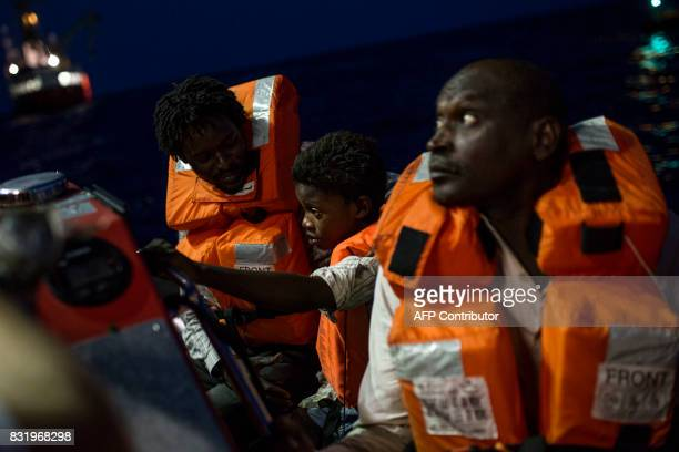 Migrants sit aboard a boat run by the Aquarius rescue ship run by NGO SOS Mediterranee and Medecins Sans Frontieres after they were rescued by NGO...