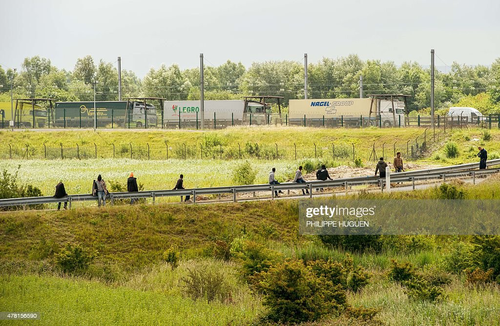 Migrants sit along the A16 highway as they try to access the Channel Tunnel on June 23, 2015 in Calais, northern France.