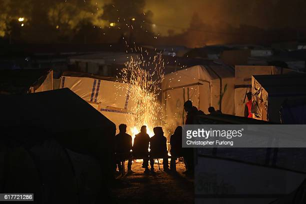 Migrants sit by a fire inside the Jungle camp on October 24 2016 in Calais France Many migrants have left by coach to be reloctated at centres across...