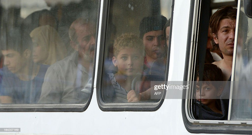 Migrants sit in a police bus after being rescued by the Armed forces of Malta at Hay Wharf in Valletta on October 12, 2013. More than 140 survivors, plucked from the sea after their overloaded boat sank in the latest deadly migrant tragedy to hit the Mediterranean, arrived in Malta. The sinking killed more than 30, most of them women and children, when the boat packed with people desperate to reach European shores went down off Malta near the Italian island of Lampedusa, according to officials.