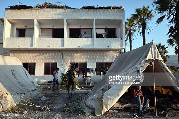 Migrants sit in front of the abandoned 'Captain Elias' hotel where migrants arriving to the Greek island of Kos found temporary shelter on August 16...