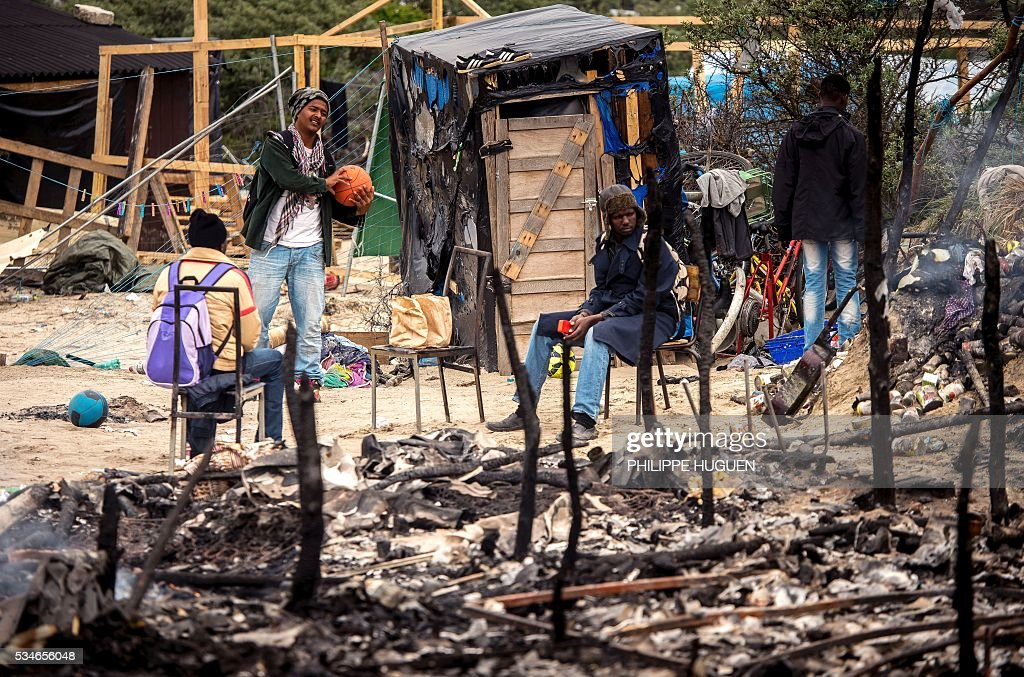 Migrants sit in the middle of burnt tents after a massive brawl that left 40 people injured in the 'Jungle' migrant camp in the northern French town of Calais on May 27, 2016. Some 20 people living in the 'Jungle' refugee camp in the northern French port of Calais were injured in a brawl between around 200 Afghans and Sudanese on May 26, 2016. / AFP / PHILIPPE