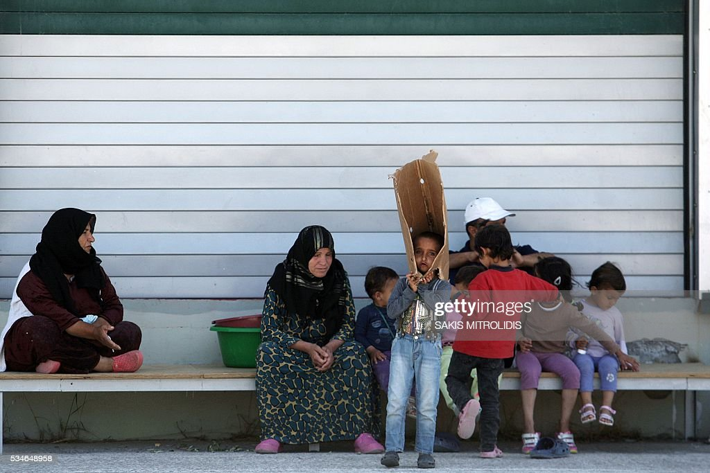 Migrants sit inside a new refugees camp in an abandoned factory in Kalohori, a west suburb of Thessaloniki on 27 May, 2016. The squalid Idomeni refugee camp in northern Greece which became a symbol of Europe's migrant crisis has been fully evacuated, police said Thursday, as another 30 died crossing the Mediterranean. In the space of three days, police transferred about 4,000 migrants by bus from Idomeni to newly created camps in the industrial outskirts of Greece's second city Thessaloniki. / AFP / SAKIS