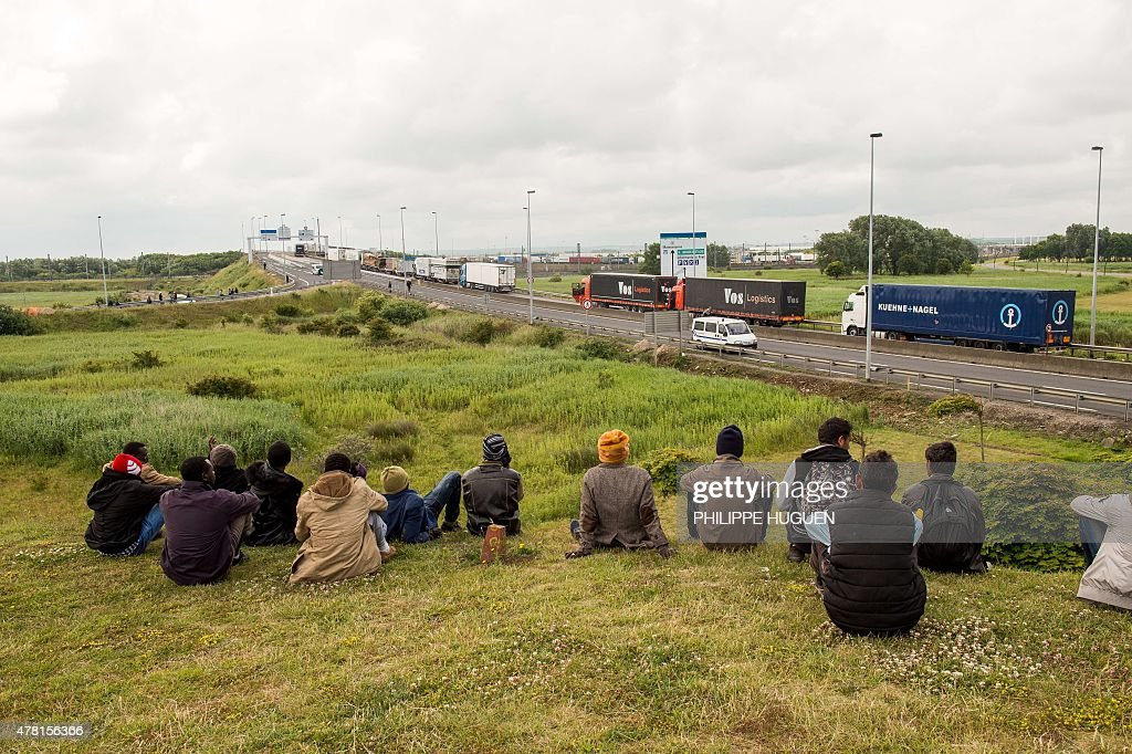 Migrants sit near the A16 highway as they try to access the Channel Tunnel on June 23, 2015 in Calais, northern France.
