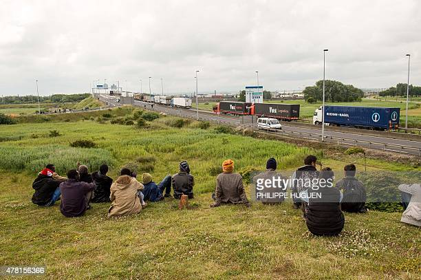 Migrants sit near the A16 highway as they try to access the Channel Tunnel on June 23 2015 in Calais northern France AFP PHOTO PHILIPPE HUGUEN
