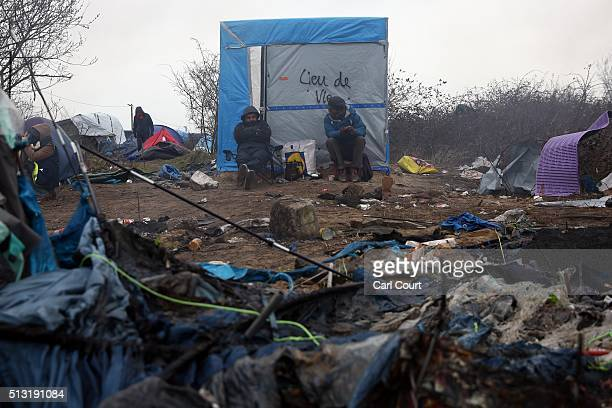 Migrants sit next to a hut as a tent smoulders in front of them in the 'jungle' migrant camp on March 01 2016 in Calais France Police and demolition...
