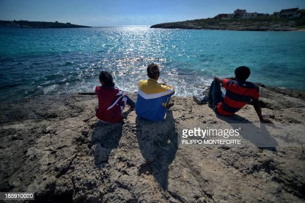 Migrants sit on rocks and stare at the sea in Lampedusa island on October 26 2013 There are currently three navy vessels on patrol along with six...