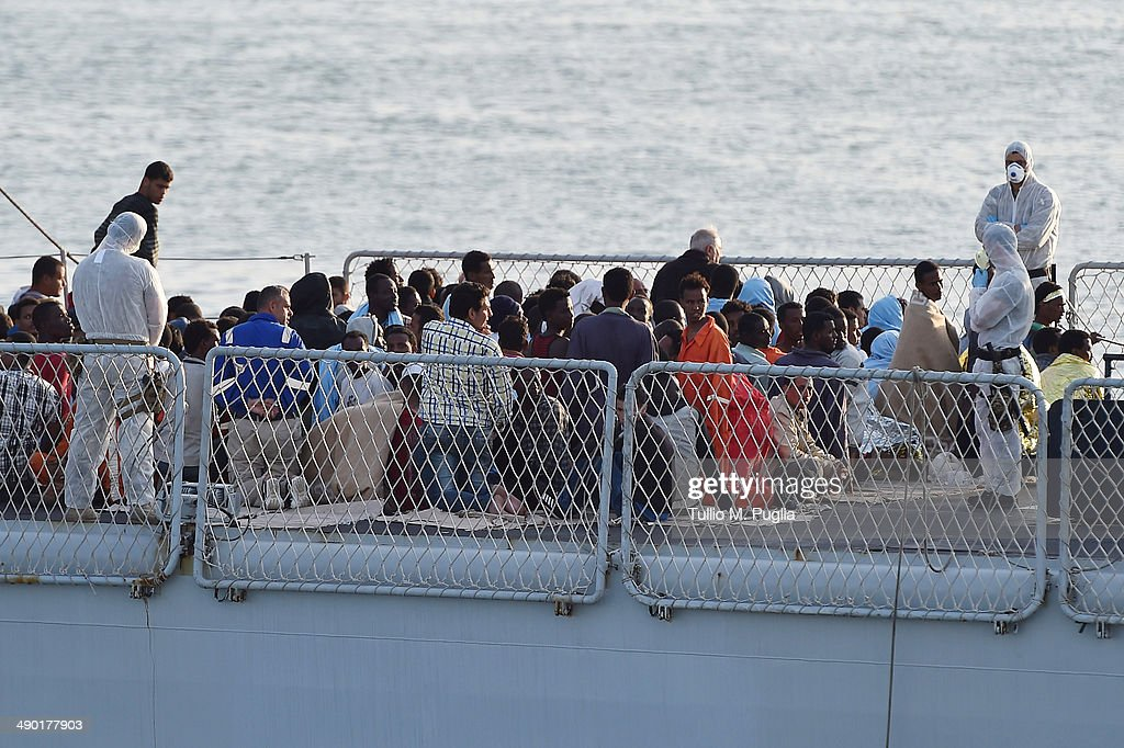 Migrants sit on the deck of Italian Navy Ship Grecale as it arrives in the Port of Catania carrying 206 migrants and 17 bodies of the victims of a...