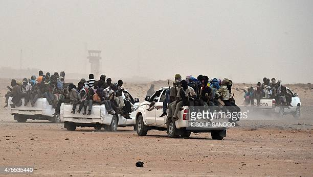 Migrants sit on the open cargo of a pickup truck holding wooden sticks tied to the vehicle to avoid falling from it as they leave the outskirts of...