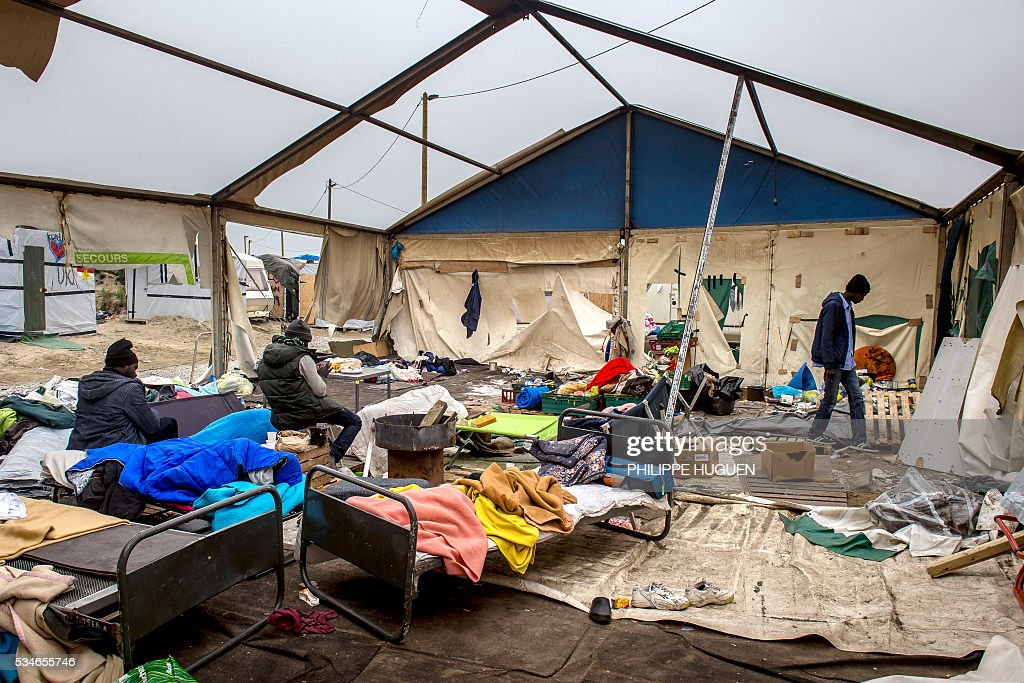 Migrants sit on their bed after a massive brawl that left 40 people injured in the 'Jungle' migrant camp in the northern French town of Calais on May 27, 2016. Some 20 people living in the 'Jungle' refugee camp in the northern French port of Calais were injured in a brawl between around 200 Afghans and Sudanese on May 26, 2016. / AFP / PHILIPPE