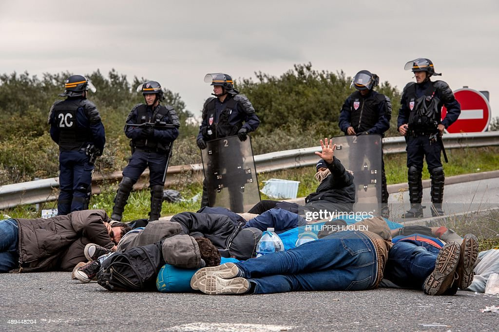 Migrants sleep on the ground after their eviction by French police officers and gendarmes from a camp site in Calais northern France on September 21...