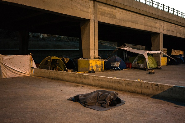 Migrants sleep on the ground next to tents in the port of Piraeus, where nearly 1,500 refugees and migrants live in a make-shift camp in Athens on July 17, 2016. In partnership with local aid group...