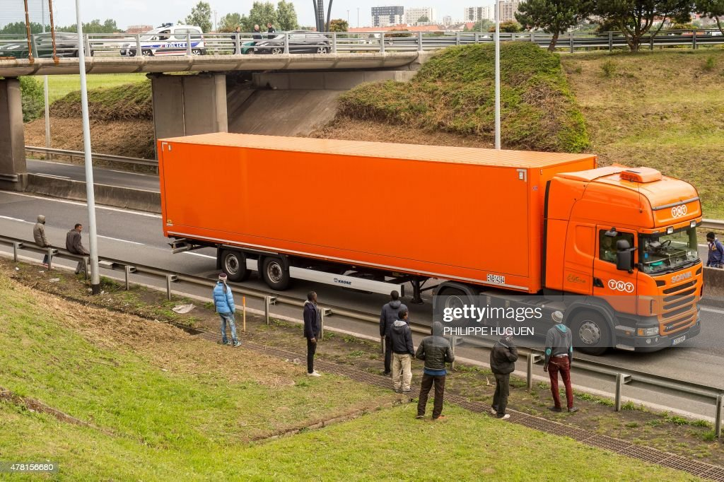Migrants stand along the A16 highway as they try to access the Channel Tunnel on June 23, 2015 in Calais, northern France.