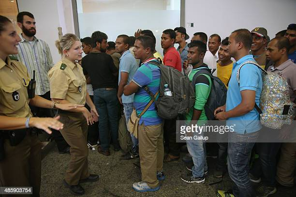 Migrants stand in a holding area after arriving at Munich Hauptbahnhof main railway station and being detained by police because the migrants had no...