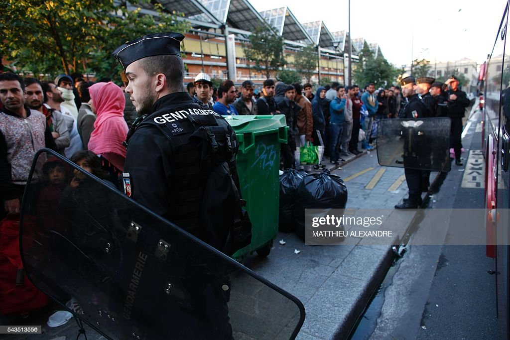 Migrants stand in line as French Gendarmes evacuate their camp on June 29, 2016 in Paris. The police started early on June 29, 2016, the evacuation of several hundreds of migrants, from a camp at the former SNCF Hall 'Pajol'. / AFP / MATTHIEU