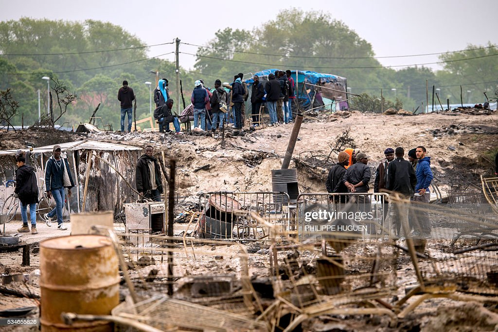 Migrants stand in the middle of burnt tents after a massive brawl that left 40 people injured in the 'Jungle' migrant camp in the northern French town of Calais on May 27, 2016. Some 20 people living in the 'Jungle' refugee camp in the northern French port of Calais were injured in a brawl between around 200 Afghans and Sudanese on May 26, 2016. / AFP / PHILIPPE