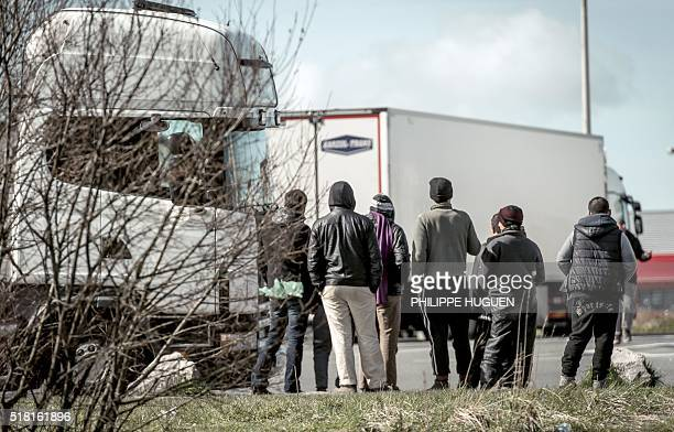 Migrants stand looking at lorries stationed in a parking lot in Marck just north of the sea port of Calais on the English Channel on March 30 2016...