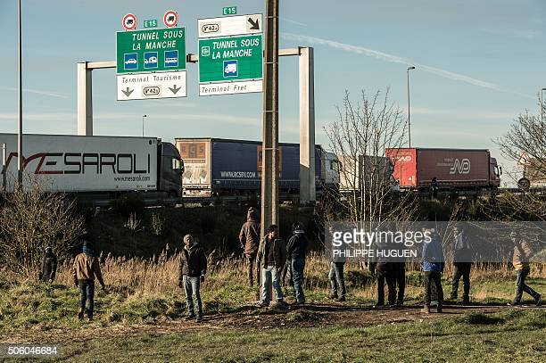 Migrants stand near the A16 motorway near the site of the Eurotunnel in Coquelles near Calais northern France on January 21 2016 Approximately 300...