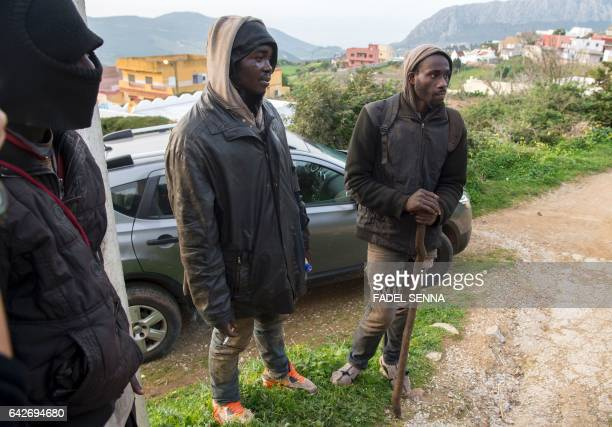 Migrants stand near the forest of the Moroccan city of Fnidek on February 18 2017 after forcing their way through a fence between Morocco and the...