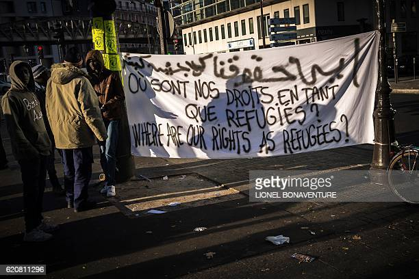 Migrants stand next to a banner on November 3 2016 in Paris near to a migrant tent camp at the Stalingrad metro station one of several camps...